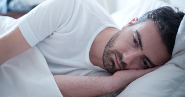 Depressed man is lying down in a bed