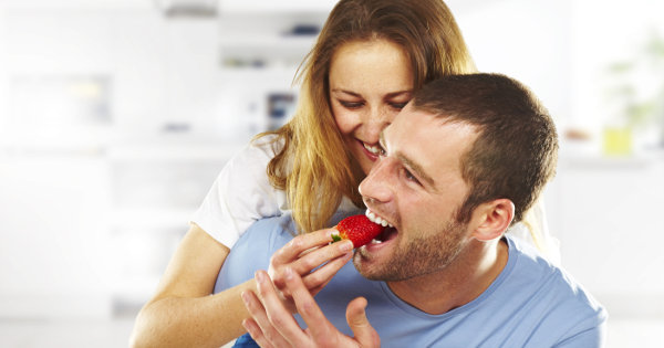Happy couple eating a strawberry